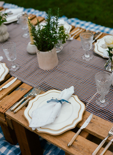 Placesetting with a rosemary plant in a Stone Container Behind it
