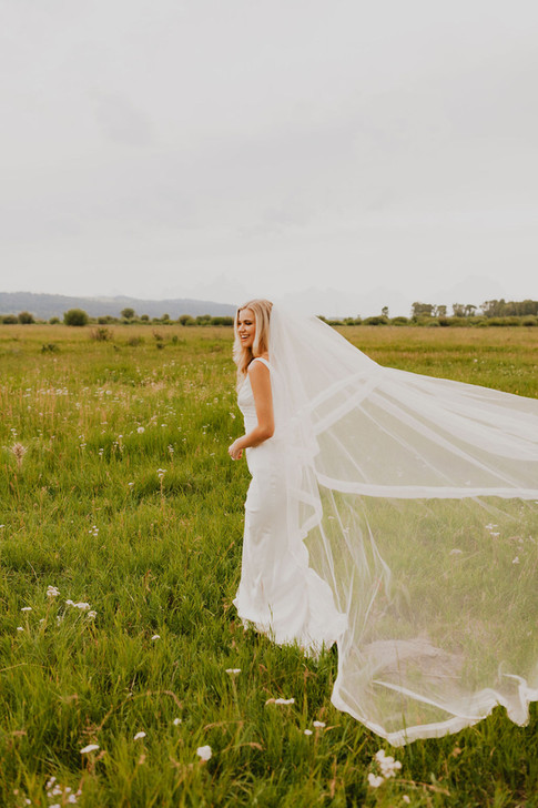 Bride Walking Through a Field with her Veil Floating Behind her