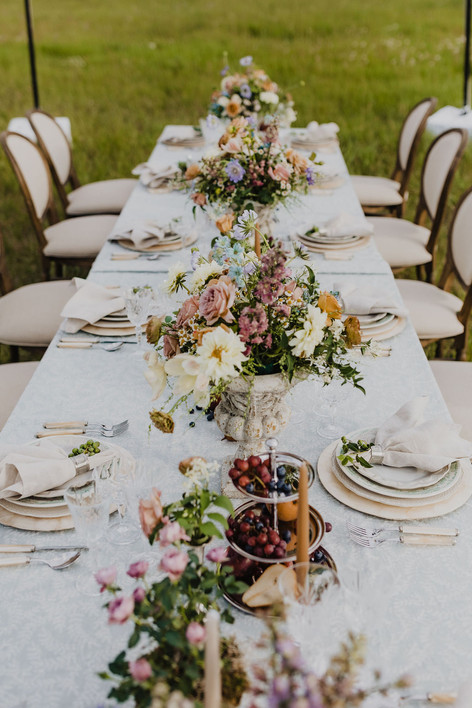 Long Table in Field with Empty Chairs, Cream and Green placesettings, Tall wild Flower Arrangements and Fruit