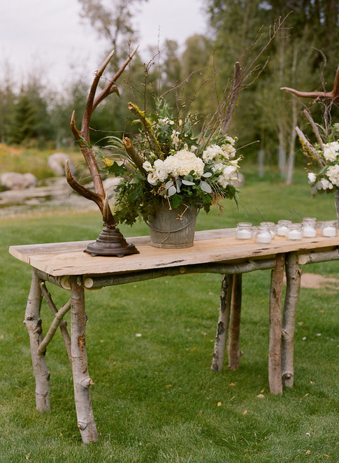 Rustic Wooden Altar Table with Standing Antler, White and Green Flower Arrangement in a metal Bucket and Tea Candles