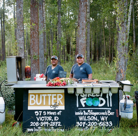 Two Chefs Behind a Food Station in a field