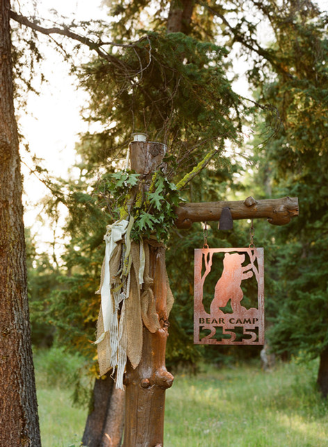 Wooden Post with a wreath of Greenery and lots of Ribbons and a Bronze Sign with a Bear Outline