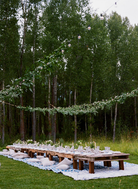 Long Low Wooden Crate Table in a Field with Lights and Greenery Above