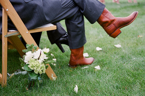 Small White and Green Aisle Flower Arrangement in front of a Chair with a Man's Legs Crossed with Brown Cowboy Boots