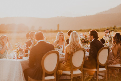 Young Men and Women at a Long Table in a Field with the Sunset Shining on Them