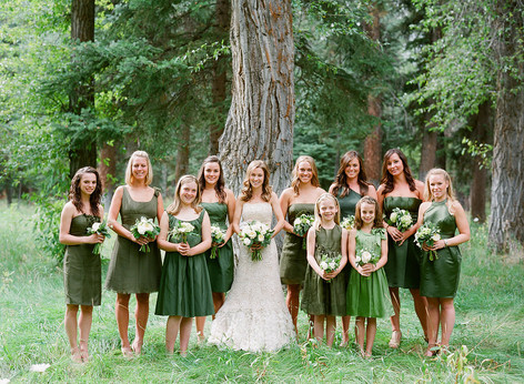 Bride with Bridesmaids in all green dresses holding Bouquets in the Woods