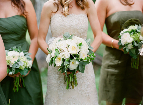 Bride Holding her White and Green Bouquet with a Bridesmaid on either side of her in a Green Dress Holding a White Bouquet