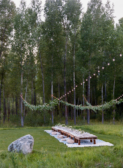 Long Low Wooden Table in a Field with String Lights Above