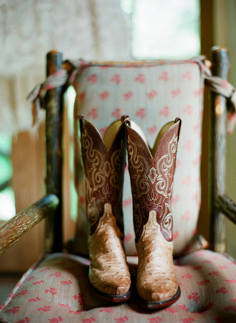 Brown Cowboy boots in Wooden Chair with Grey and Red Flowered Cushion