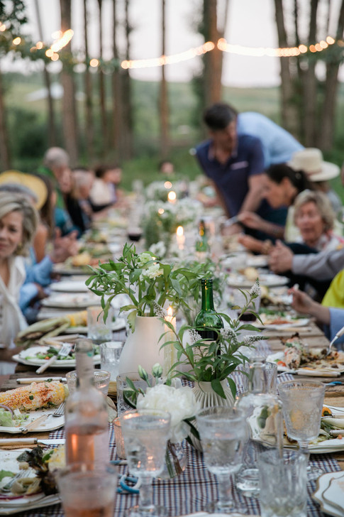 People Eating and Drinking at a Long low Table in a Field