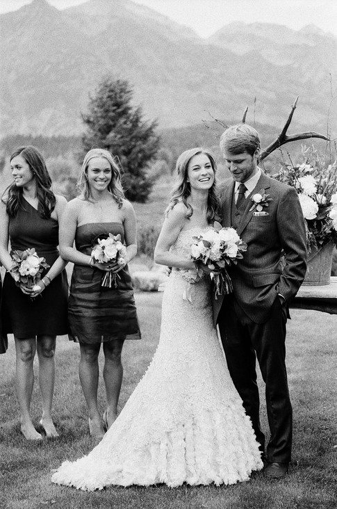 Bride and Groom Smiling and Hugging with Bridesmaids Smiling Behind them