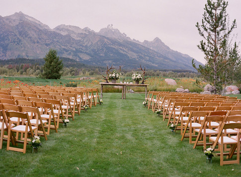 Atlar Table with Flowers and Antlers at a Wedding Ceremony Site on a :awn in Front of the Teton Mountains