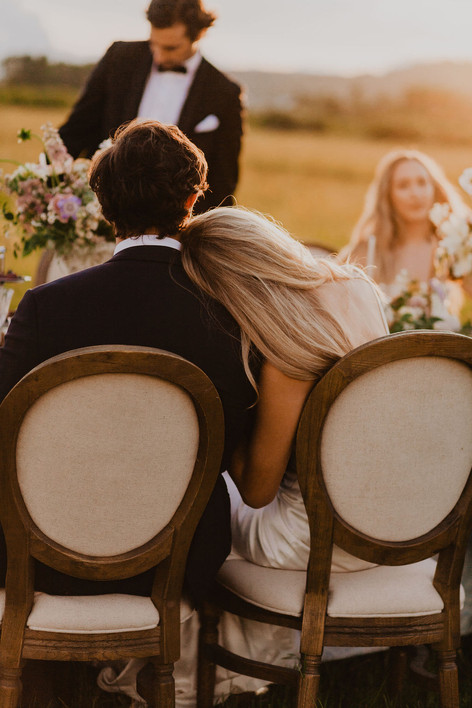Bride Sitting in an Upholstered Wooden Chari Leaning her Head on The Grooms Shoulder Sitting Next to Her