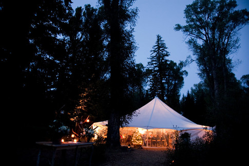 White Tent Lit up in the Woods in the Evening