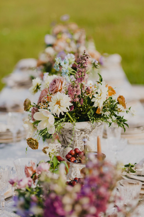 Wild, Romantic Yellow and Pink Flower Arrangments Lining a Long Table