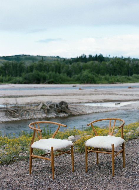 Two Wooden Wishbone Chairs with Shearling Seats on a Riverbank