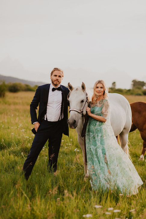 Young Blong Man and Blond Woman Stand with a White Horse in a Field