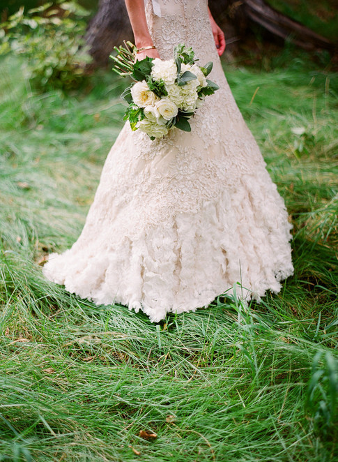 Bride Walking on Green Grassy Woodland Holding Her Bouquet at Her Side