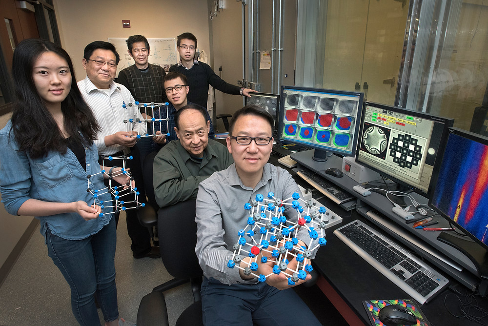 Clockwise from left, Stony Brook University student Jing Li and Brookhaven Lab scientists Hong Gan, Qingping Meng, Enyuan Hu, Ke Sun, Xiao-Qing Yang, and Dong Su in an electron microscopy lab at the Center for Functional Nanomaterials. The molecular models they are holding correspond to the phases that emerged within a single magnetite nanoparticle as lithium ions were added. Not pictured: Eric Stach, Kai He, Yimei Zhu, and Xiqian Yu, Brookhaven Lab; Christopher Murray and Sen Zhang, University of Pennsylvania; Yifei Mo and Yizhou Zhu, University of Maryland, College Park.