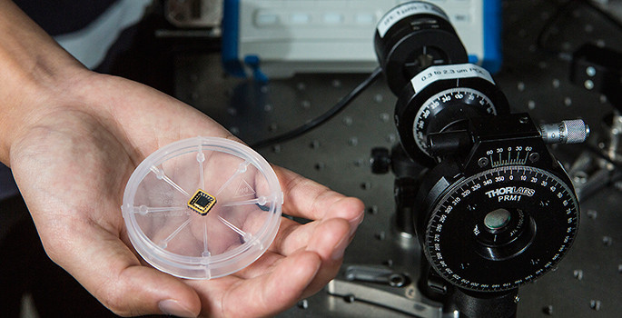 The chip in the hand does the same job as the conventional circularly polarized light detector on the right. (Anne Rayner / Vanderbilt)