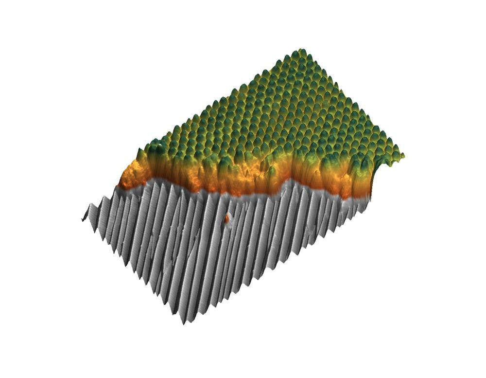 Composition of the nanostructure: On the approximately 10 nanometres (nm) deep grooves of an aluminium oxide (grey) a 40nm thick layer of copolymers (brown) is deposited, internally forming chemical domains. On suitable domains, metal nanodots (green) grow. Here, they reached a height of about 10nm. The area shown measures 3000nm by 1800nm. Credit: Denise Erb, DESY