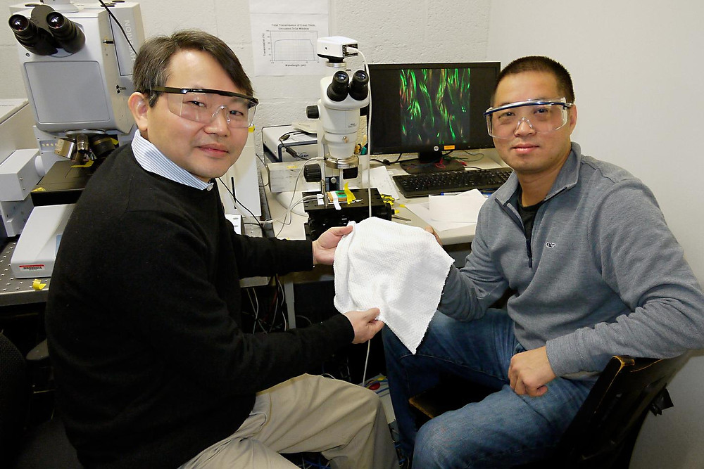 University of Maryland Chemistry and Biochemistry Professor YuHuang Wang (left) and Physics Professor Min Ouyang hold a swatch of their new fabric that can automatically adjust its insulating properties to warm or cool a human body.  @ Faye Levine, University of Maryland