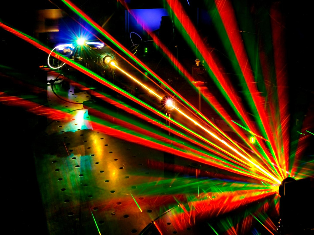A twisted laser beam hits a nanoscopic U-shaped gold grating which further twists the beam in either a right or left-handed direction. This deflects the beam in many directions and further splits it into its constituent wavelengths across the color spectrum.  @ Ventsislav Valev