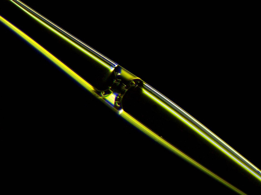 Photograph of a fluid meniscus inside an opto-mechano-fluidic resonator (OMFR) made of high purity silica glass. Particles flowing through the internal microchannel can be detected optically at extremely high speed. @ University of Illinois