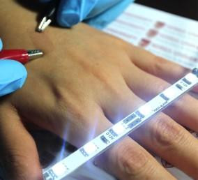 Highly conductive ultrathin film on skin between clips.