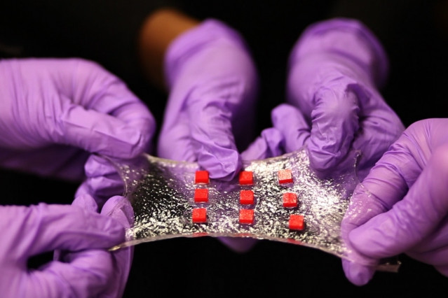 A new stretchy hydrogel can be embedded with various electronics. Here, a sheet of hydrogel is bonded to a matrix of polymer islands (red) that can encapsulate electronic components such as semiconductor chips, LED lights, and temperature sensors.  Credit: Melanie Gonick/MIT