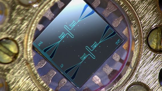 Photo of a centimeter-sized silicon chip, which has two parallel superconducting resonators and quantum-circuit refrigerators connected to them. @ Kuan Yen Tan.