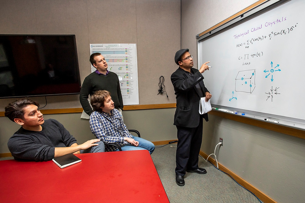 Princeton University Professor Zahid Hasan, right, describes the exotic behavior of electrons in topological crystals that were studied at Berkeley Lab. Members of Hasan's research team observe, including: Daniel S. Sanchez (left), Ilya Belopolski (standing, middle), and Tyler A. Cochran (seated, middle). (Credit: Marilyn Chung/Berkeley Lab)