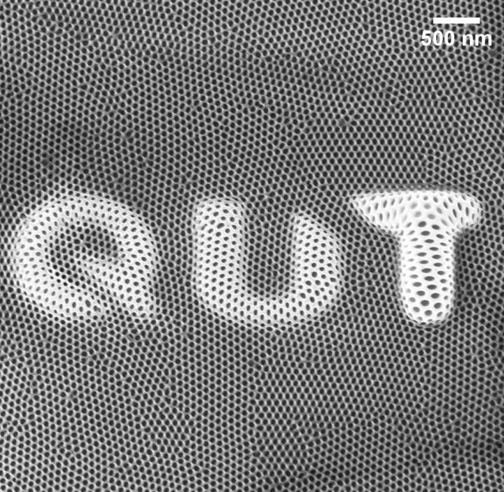 This is the QUT logo formed by exposure of anodised alumina material to helium ions.  @ QUT