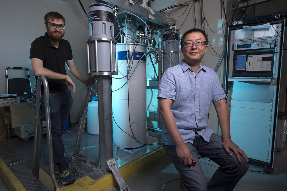 UCI physicist Jing Xia (right, with graduate student Alex Stern) calls the fiber-optic Sagnac interferometer he built the most sensitive magnetic microscope in the world. He compares it to a telescope that an ornithologist in Irvine could use to inspect the eye of a bird in New York. @ Steve Zylius / UCI
