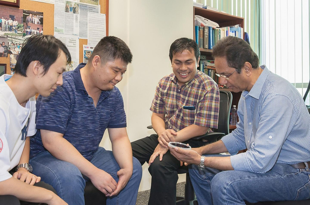 Part of the team members from NUS Nanoscience and Nanotechnology Institute are: (from left to right) Dr. Renshaw Wang, Dr. Huang Zhen, Assistant Professor Ariando and Professor T. Venkatesan. They are looking at a four-inch wafer on which a multi-component oxide film has been deposited using the pulsed laser deposition process.