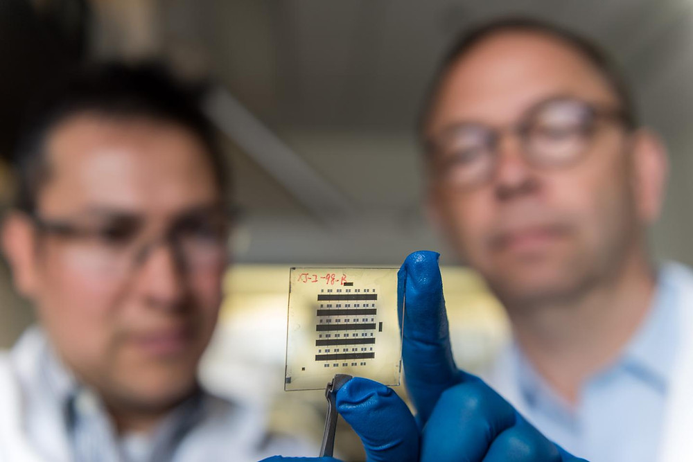 Georgia Tech Senior Research Scientist Canek Fuentes-Hernandez (left) and Professor Bernard Kippelen examine a sample of organic thin-film transistors created with a new nanostructured gate dielectric that gives the devices unprecedented stability.  @ Rob Felt, Georgia Tech