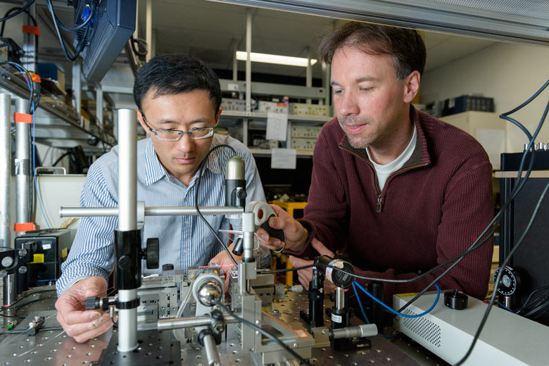 Postdoctoral scholar Leo Yu, left, and senior research scientist Carsten Langrock epoxy optical fibers to a nonlinear optical waveguide that converts the wavelength of a single-photon signal to a common telecom wavelength, thereby enabling communication to a next node over long distances.