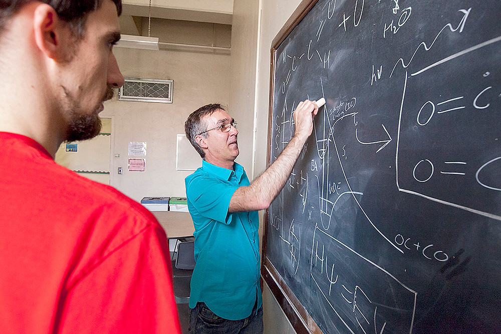 Sanov draws out the chemical reaction and formula of the long elusive ethylenedione (OCCO) four-atom compound to team members Andrew Dixon, a doctoral student in chemistry, and Tian Xue, an undergraduate majoring in chemistry. The students were instrumental to Sanov's research on discovering proof of the long-elusive compound. (Photo: John de Dios/UANews)