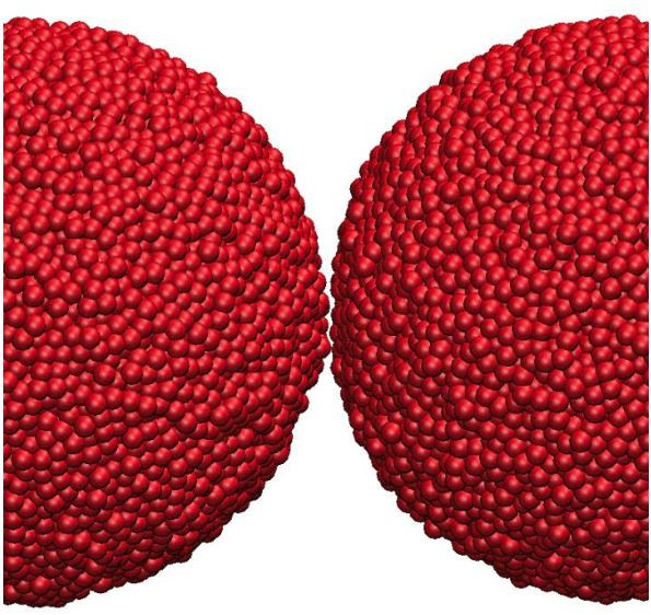 A digital reconstruction shows how individual atoms in two largely spherical nanoparticles react when the nanoparticles collide in a vacuum. In the reconstruction, the atoms turn blue when they are in contact with the opposing nanoparticle.  @ Yoichi Takato