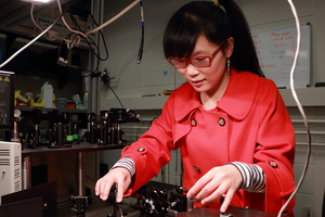 MIT physics graduate student Qiong Ma, who is part of Associate Professor Pablo Jarillo-Herrero's group, is doing original research on the electrical properties of graphene-based devices in combination with hexagonal boron nitride, using laser light stimulation. Photo: Denis Paiste/Materials Processing Center