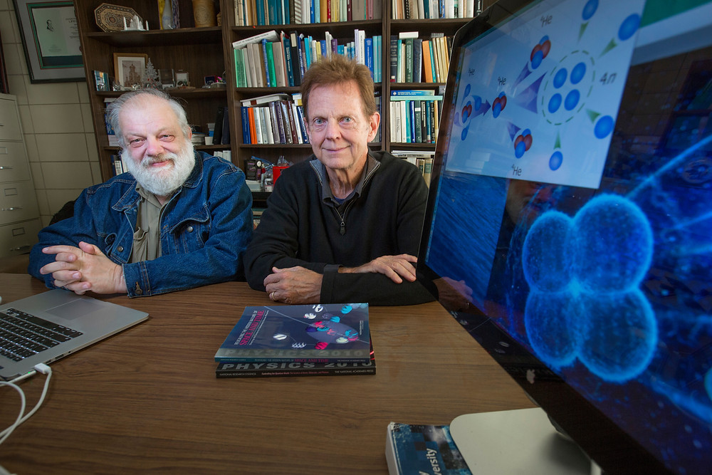 James Vary, right, and coauthor Andrey Shirokov with an illustration of a tetraneutron. @ Christopher Gannon/Iowa State University
