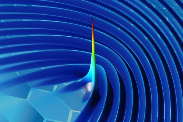 """By using plasmons to """"wiggle"""" a free electron in a sheet of graphene, researchers have developed a new method for generating X-rays. In this image of one of their simulations, the color and height represent the intensity of radiation (with blue the lowest intensity and red the highest), at a moment in time just after an electron (grey sphere) moving close to the surface generates a pulse.  Courtesy of the researchers"""