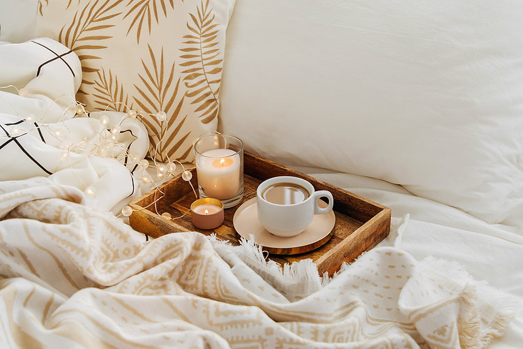 Wooden tray of coffee and candles on bed. White bedding sheets with striped blanket and pi