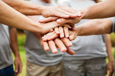 People's hands together in team handshake