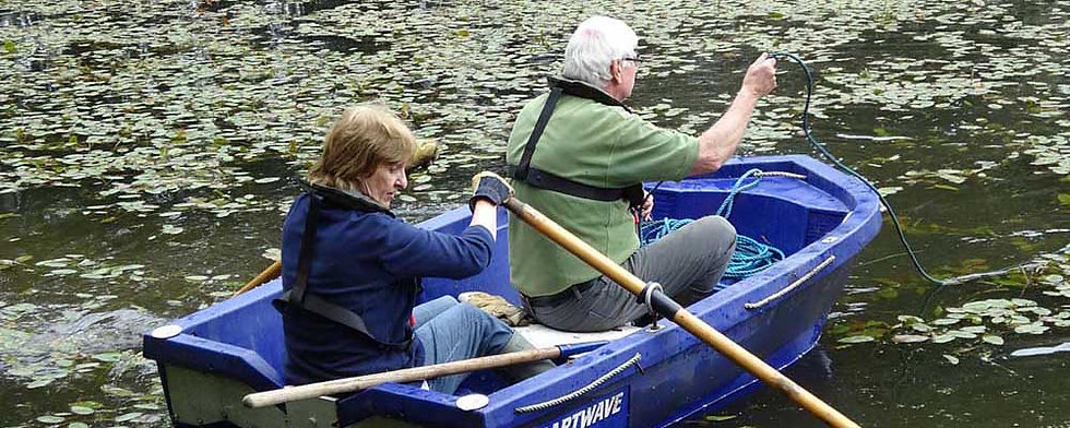 Photo of a woman and a man in a rowing boat during a club working party. Equal opportunities at Rhyl and St Asaph angling association.