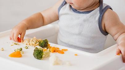 cute-baby-boy-highchair-choosing-what-eat.jpg