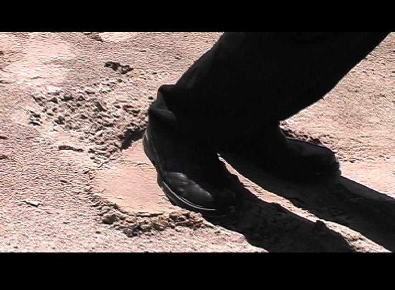 Schattengymnastik Der Künstler ändert seine Körperstellung in der Vertikalen so, dass sein Schattenbild immer an der gleichen Stelle bleibt, obwohl die Sonne wandert.