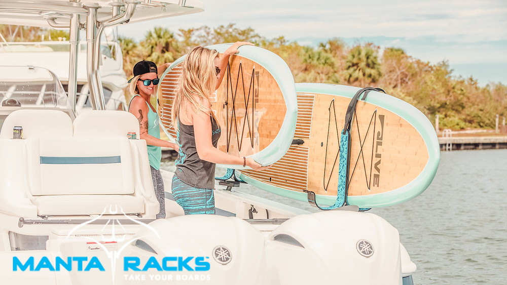 girls installing Stand up paddle board on Manta rack system on boat.