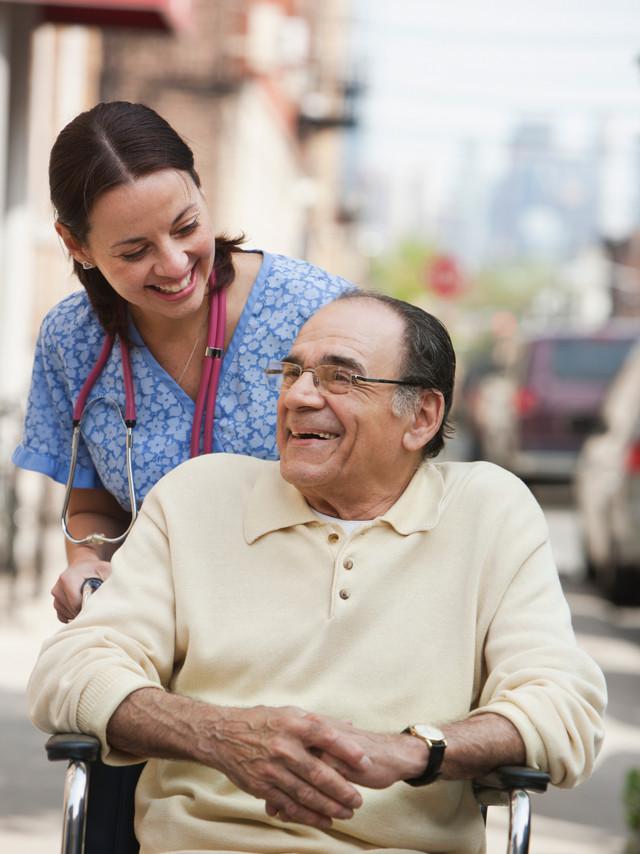 Home health nurse helping man in wheelchair