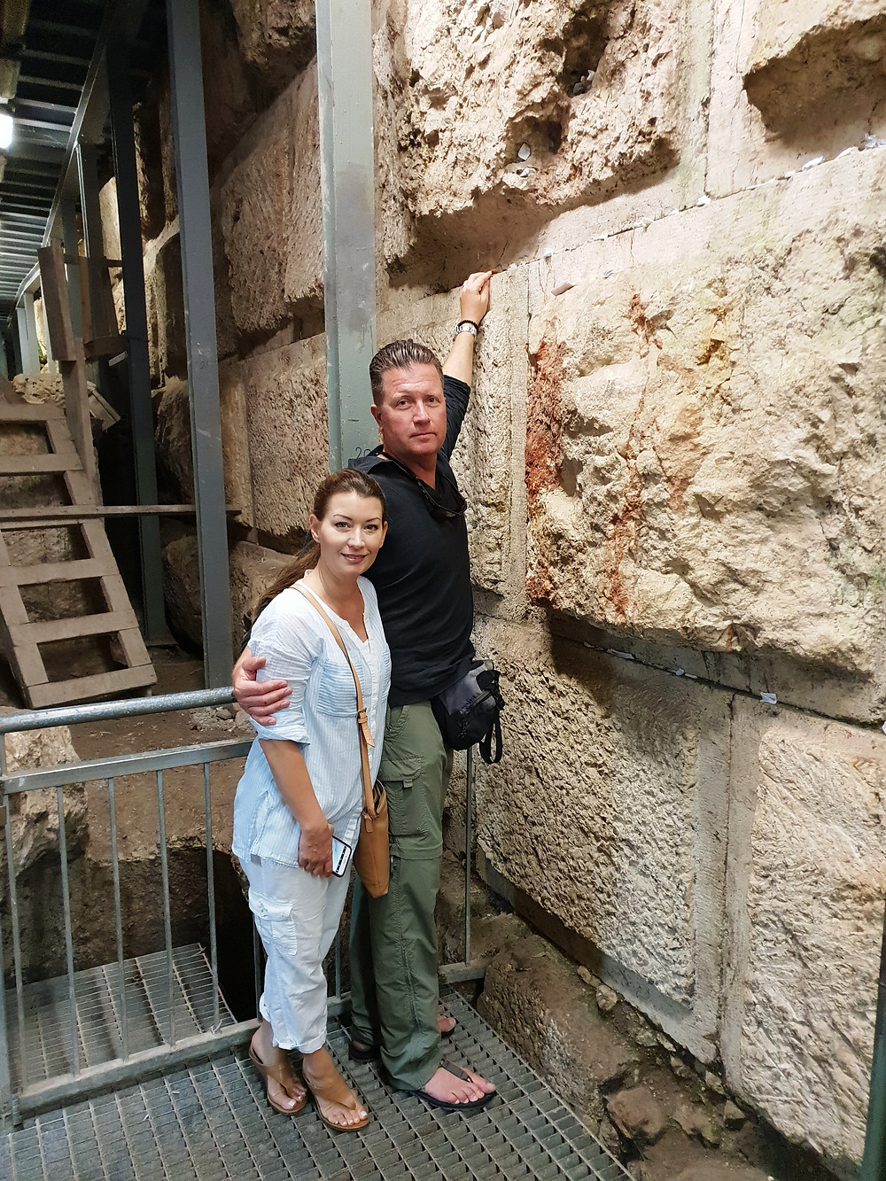 A couple from NY puts a wish note between the stones of the Western Wall at the Secret Tunnel
